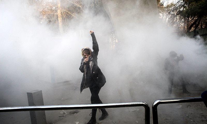 ایک خاتون آنسو گیس سے بچنے کی کوشش کر رہی ہے — فوٹو، اے پی
