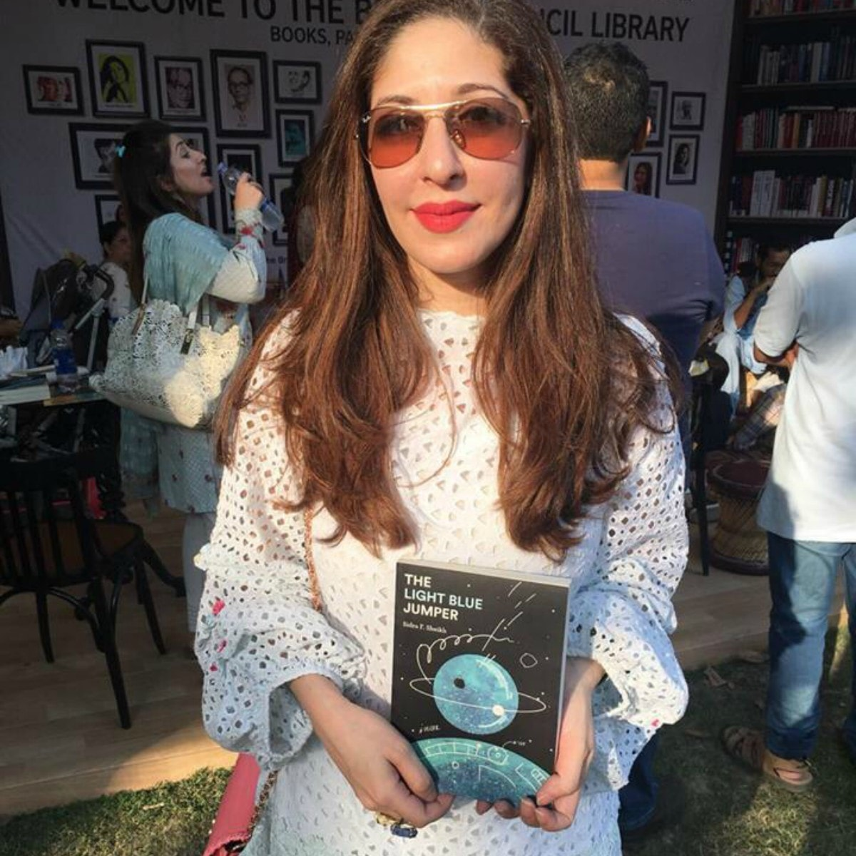 Sidra Sheikh with a copy of her sci-fi novel The Light Blue Jumper at a pop-up library in Lahore — Photograph courtesy Mongrel Books