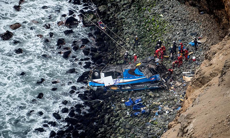Rescuers, police and firefighters work at the scene after a bus plunged around 100 meters over a cliff when it collided with a truck on a coastal highway. ─ AFP