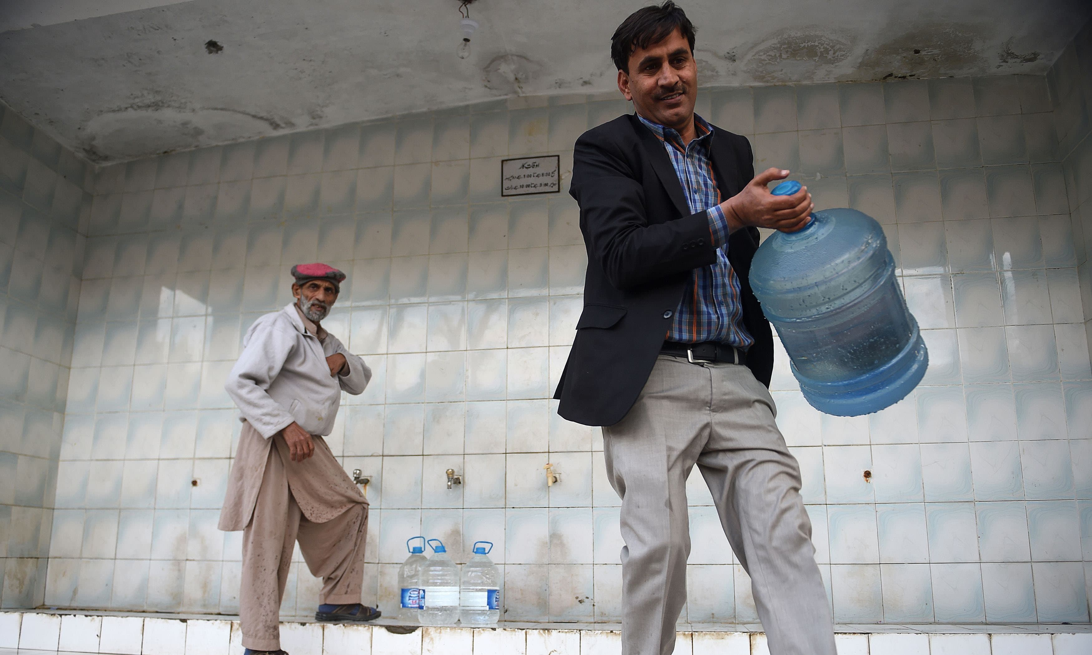 A man carrying a bottle at a water filtration plant in Islamabad. — AFP