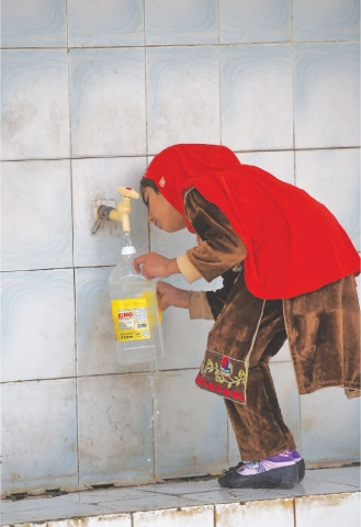 A girl fills a bottle at a water filtration plant in Islamabad.—AFP
