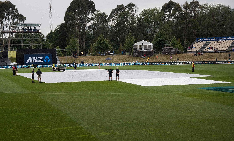 بارش کے سبب وکٹ کو کورز سے ڈھانپ دیا گیا تھا اور میچ  ڈیڑھ گھنٹے تک دوبارہ شروع نہیں ہو سکا— فوٹو: اے ایف پی