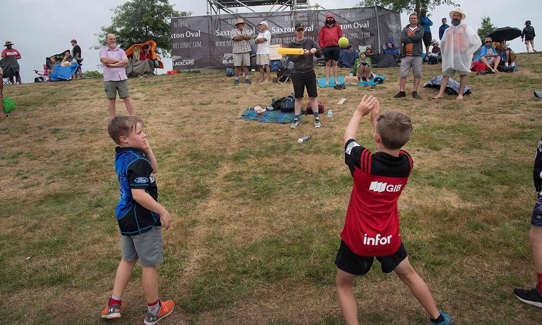 بارش کے سبب میچ رکنے پر شائقین کرکٹ کھیلتے ہوئے بھی دیکھے گئے— فوٹو: اے ایف پی