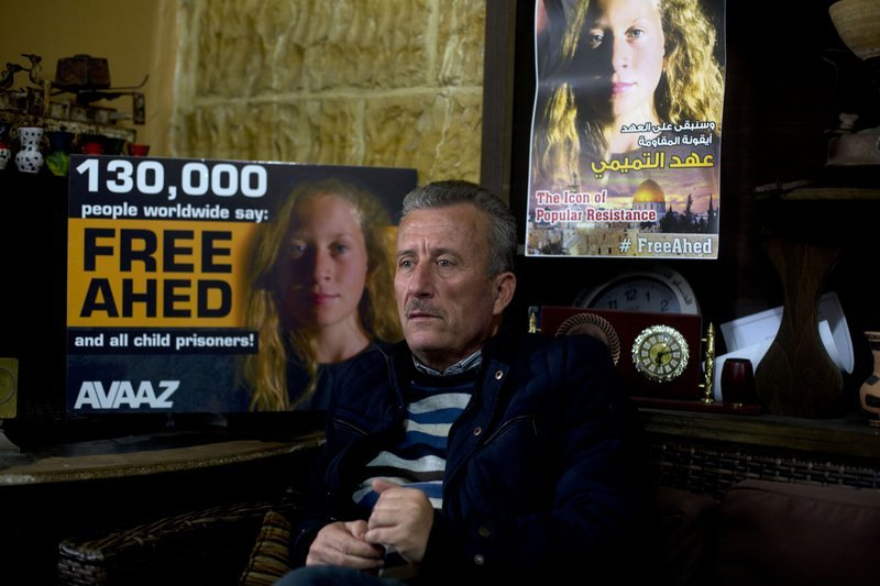 Palestinian Bassem Tamimi speaks in front of a poster showing his daughter Ahed at his home in Nabi Saleh near the West Bank city of Ramallah.─AP