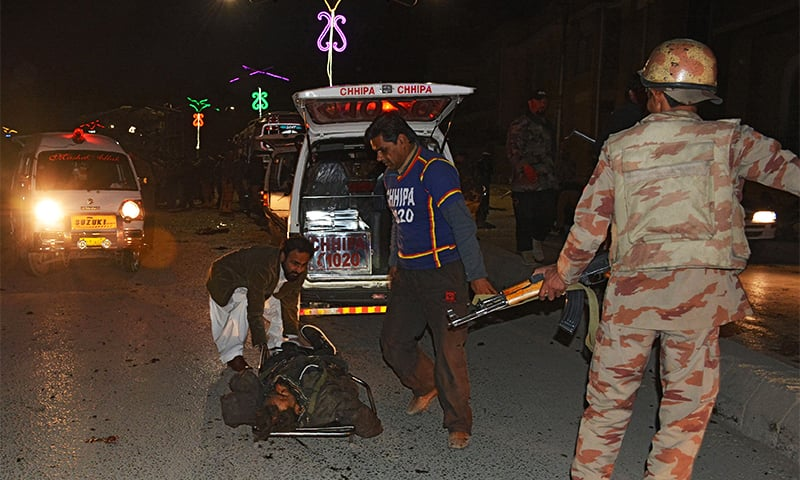 Volunteers move the body of a policeman at the site of the suicide bomb attack in Quetta. — AFP