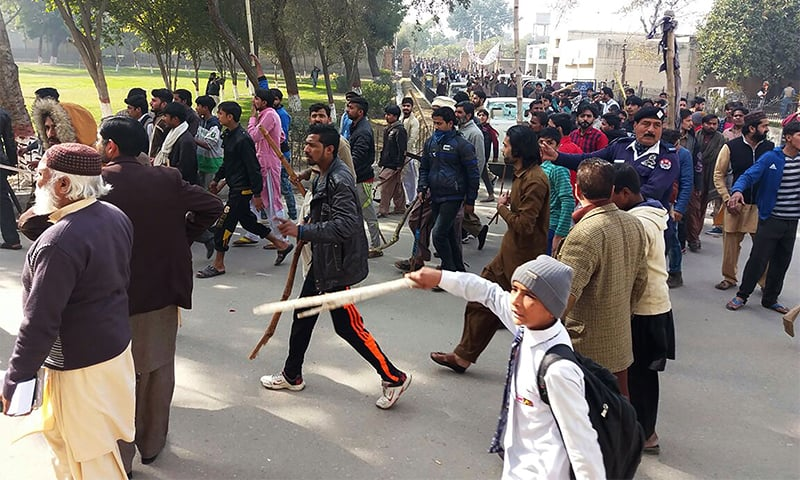 People hold bamboo sticks as they stage a protest against Zainab's murder.— AFP