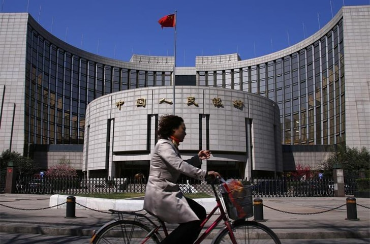 A woman rides past the People's Bank of China headquarters in Beijing. The Chinese are urging Pakistan to expand the role of the yuan in the economy from trade and investment payments to reserve currency, and even asking for it to be made a legal tender in Gwadar, a demand that has not yet been accepted.—Reuters