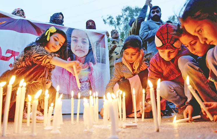 Children light candles at a vigil for Zainab at Karachi Company on Thursday. — Photo by Mohammad Asim