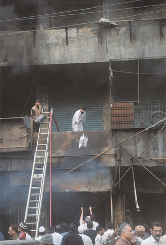 Men at the scene of a fire at Empress Market