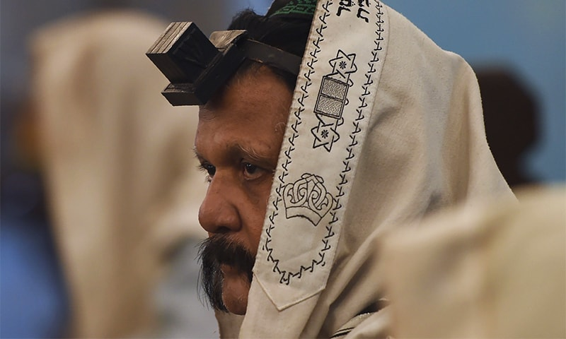 A member of the Indian Jewish community with the tefillin on his forehead attends a morning prayer service at the Magen David Synagogue in Mumbai. ─ AFP