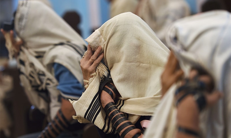 A member of the Indian Jewish community touches the tefillin on his forehead during a morning prayer service at the Magen David Synagogue in Mumbai. ─ AFP