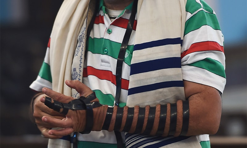 A member of the Indian Jewish community binds the tefillin on his hand before a morning prayer service at the Magen David Synagogue in Mumbai. ─ AFP