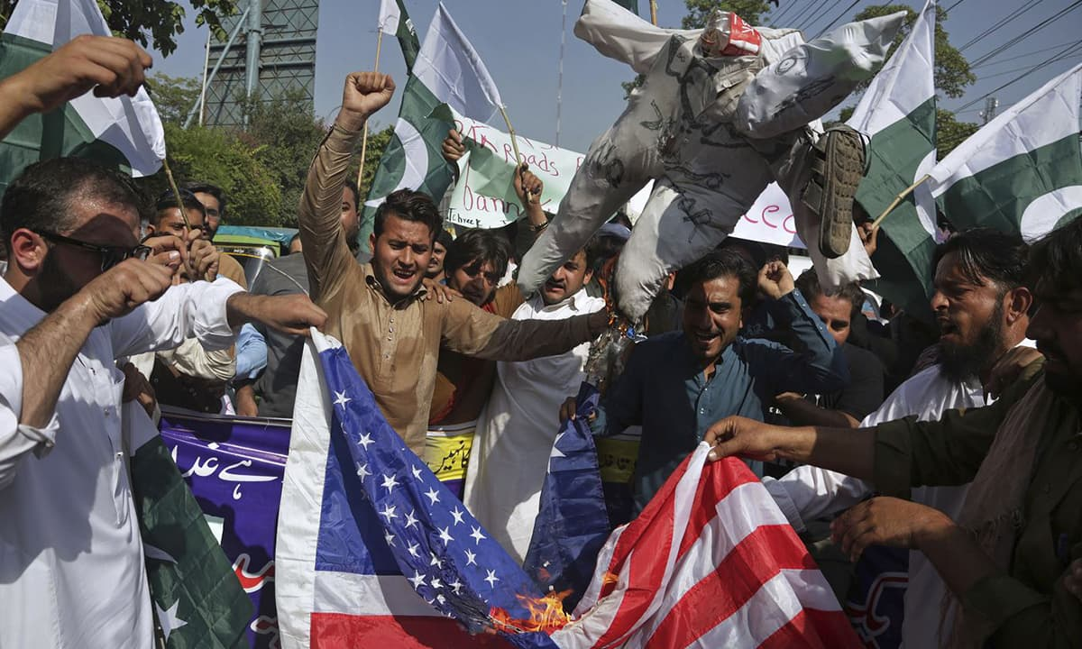 Pakistani protesters burn the American flag and an effigy of US President Donald Trump during an anti-US demonstration in Lahore on August 27, 2017 | AP