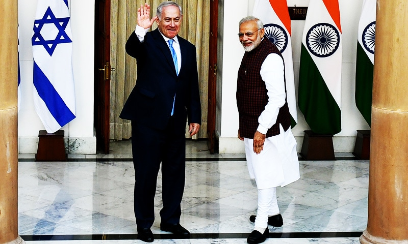 Indian Prime Minister Narendra Modi looks on as Israeli Prime Minister Benjamin Netanyahu waves ahead of a meeting.—AFP