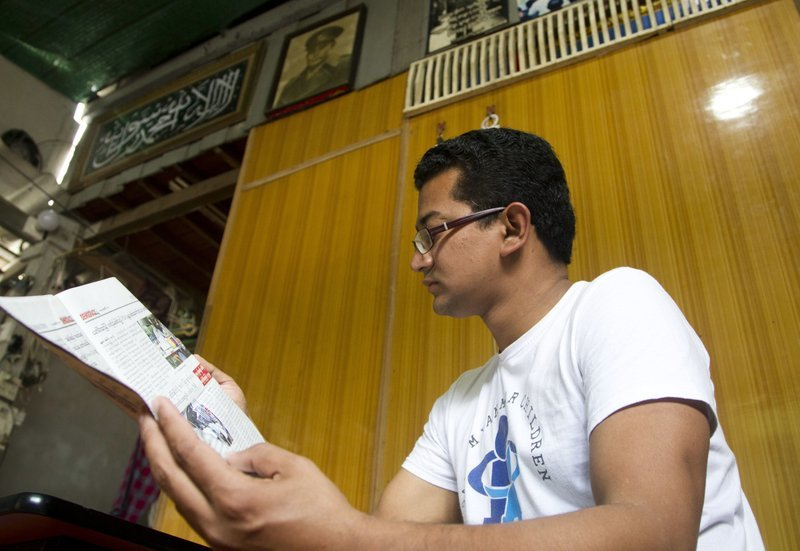 In this Jan 7 photo, Sithu Maung, a former student activist who spent more than four years in prison, reads a local journal at his residence in Yangon, Myanmar.─AP
