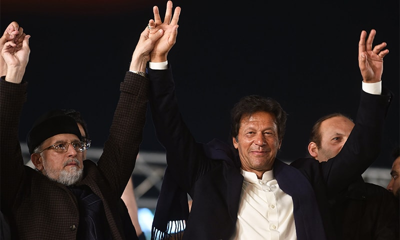 PAT chief Tahirul Qadri and PTI Chairman Imran Khan raise hands during an anti-government protest rally in Lahore on Wednesday.— AFP