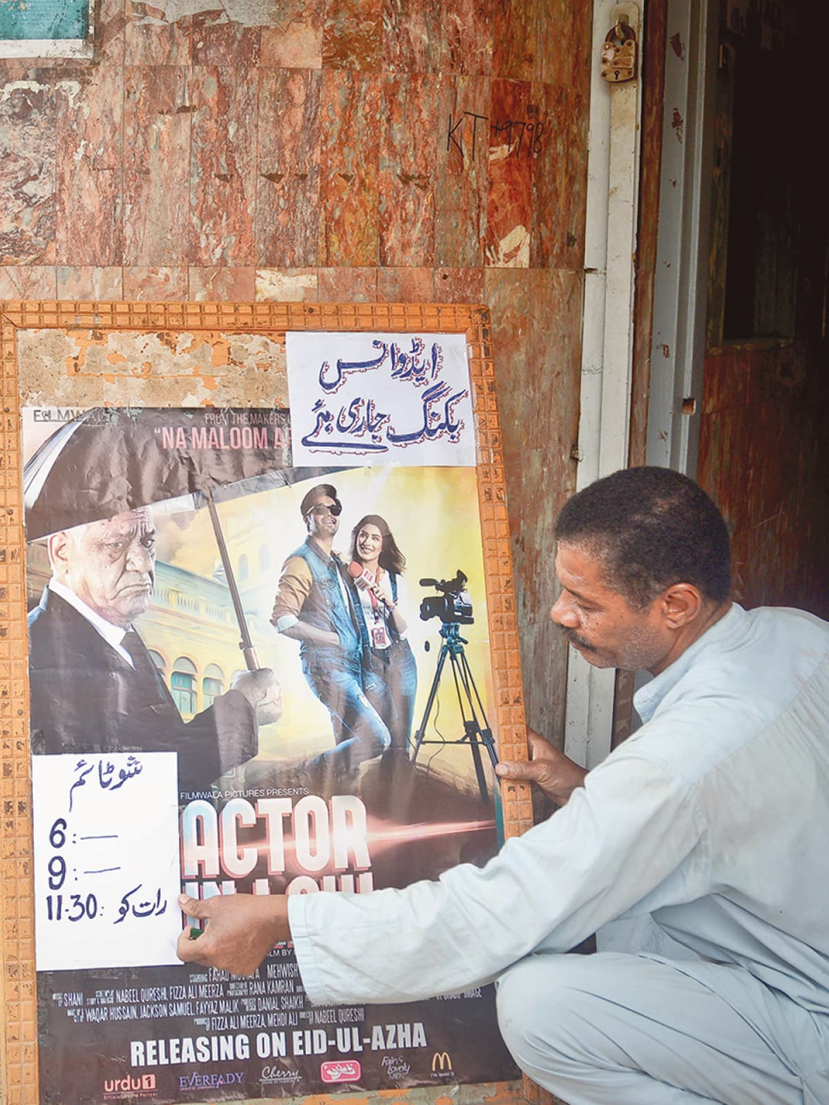A man puts up a notice announcing showtimes outside a cinema house | Fahim Siddique, White Star