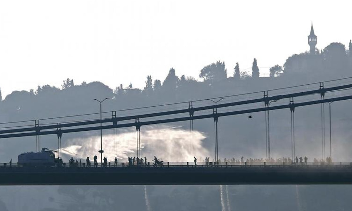 An armoured police vehicle uses a water canon to disperse anti-government demonstrators on the Bosphorous Bridge, Istanbul, in 2016  | Reuters