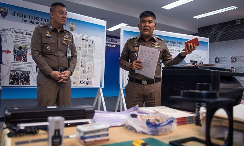 Commander of the Immigration Bureau, Lt. Gen. Suttipong Vongpint (R), holds a fake Singaporean passport during a press conference in Bangkok.— AFP
