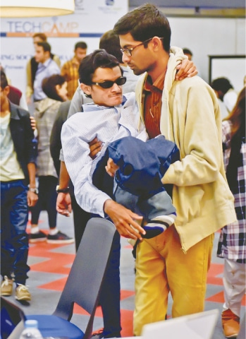 A physically challenged person is being helped to take a seat at the TechCamp.—Fahim Siddiqi / White Star
