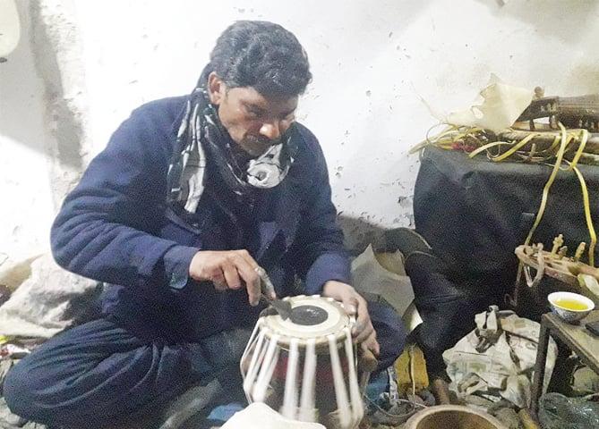 An artisan makes a tabla at his workplace in Peshawar. — Dawn