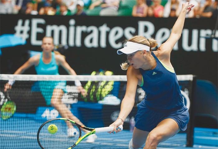MELBOURNE: Denmark's Caroline Wozniacki hits a return to Magdalena Rybarikova of Slovakia during their Australian Open match at the Rod Laver Arena on Sunday.—Reuters