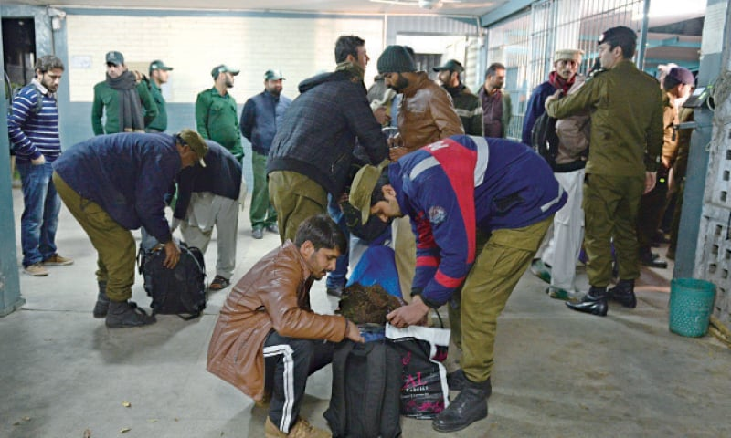 Police check the bags of students during a search operation in a Punjab University hostel. — White Star