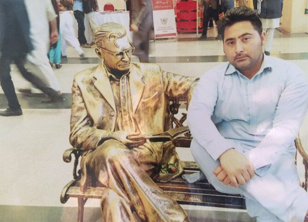 Mashal Khan sitting next to a public sculpture in Moscow in Pakistani attire