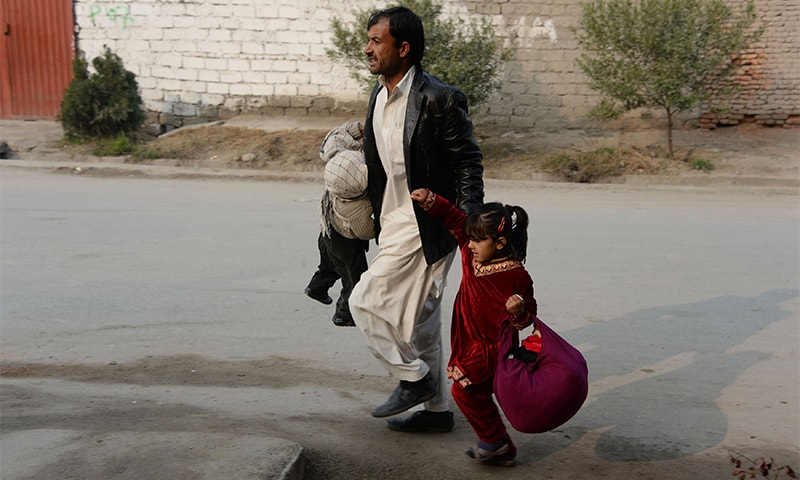 An Afghan man runs with two children near an office of the British charity Save the Children during an ongoing attack.— AFP