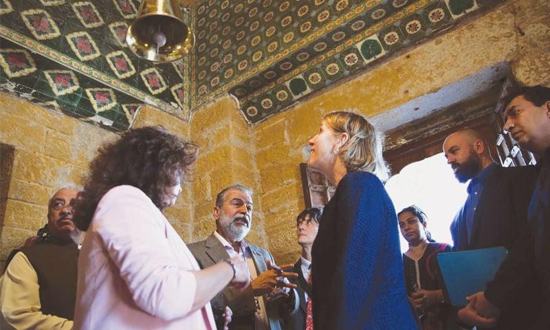 UNITED States Consul General Grace Shelton looks at the restored ceiling of Varun Dev Mandir at Manora on Thursday as Dr Kaleemullah Lashari and  Dr Asma Ibrahim brief her.—PPI