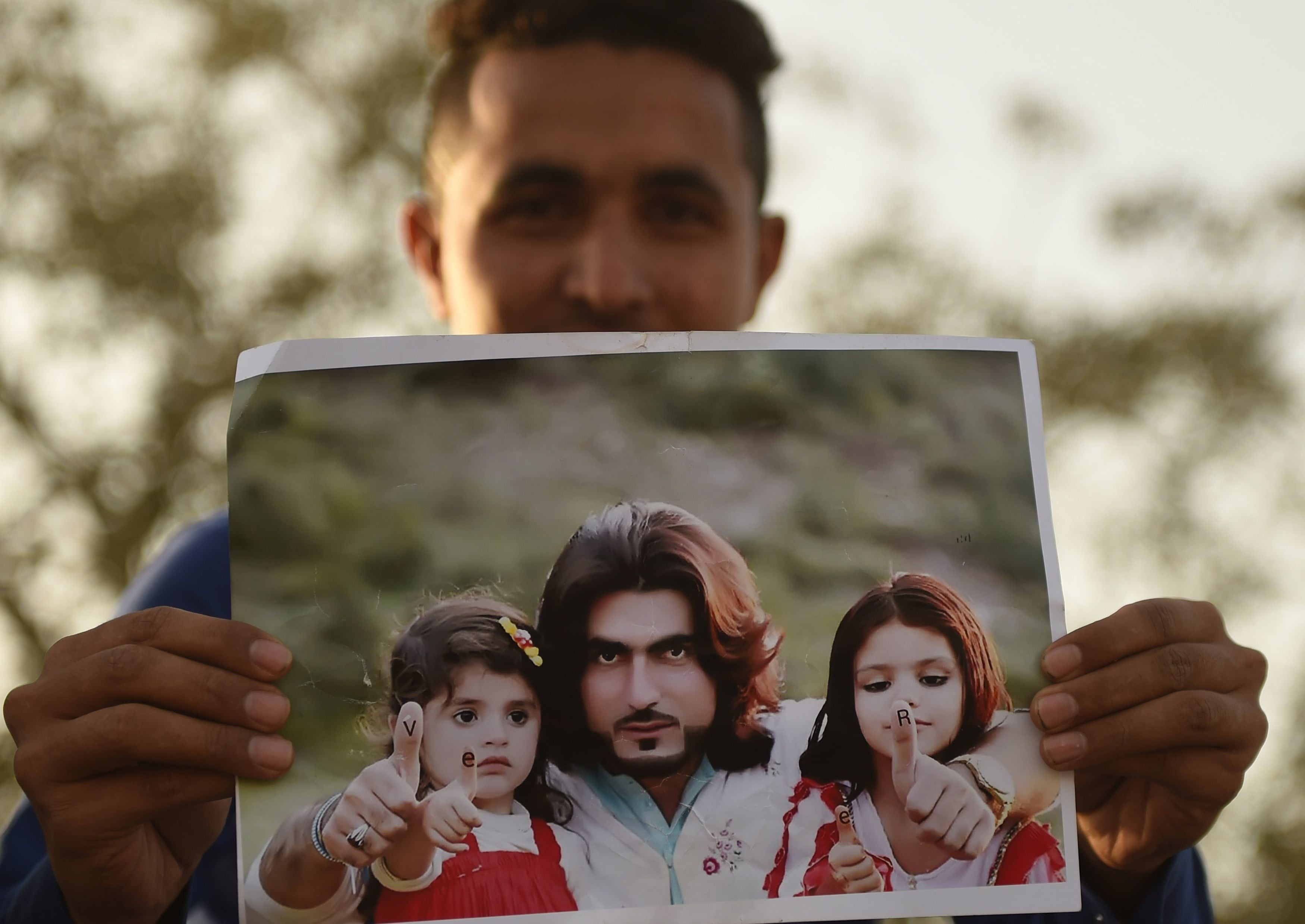 A protester holds a photograph of Naqeebullah Mehsud — AFP