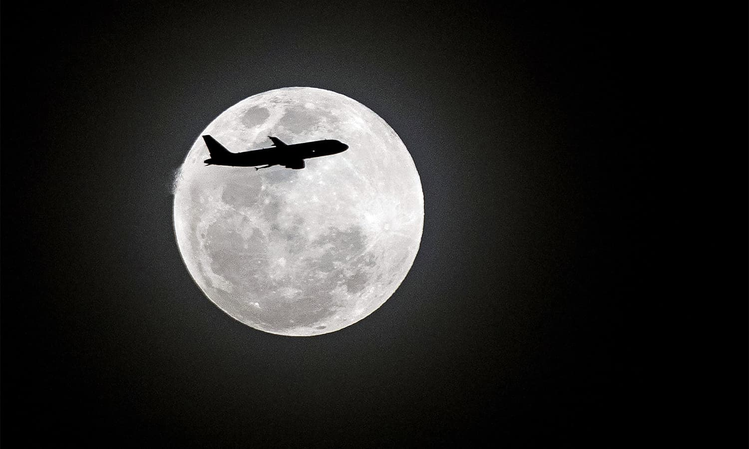 A commercial plane flies in the sky as a full moon is seen in Manila on January 31.— AFP