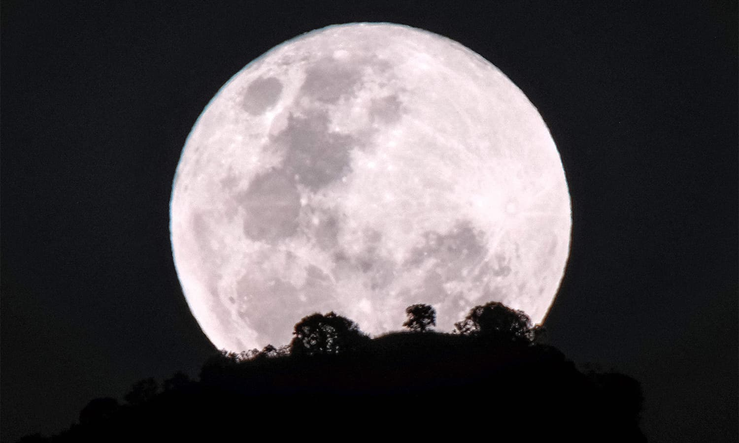 The moon rises over Kadam mountain in Nakapiripirit town, northeastern Uganda.— AFP