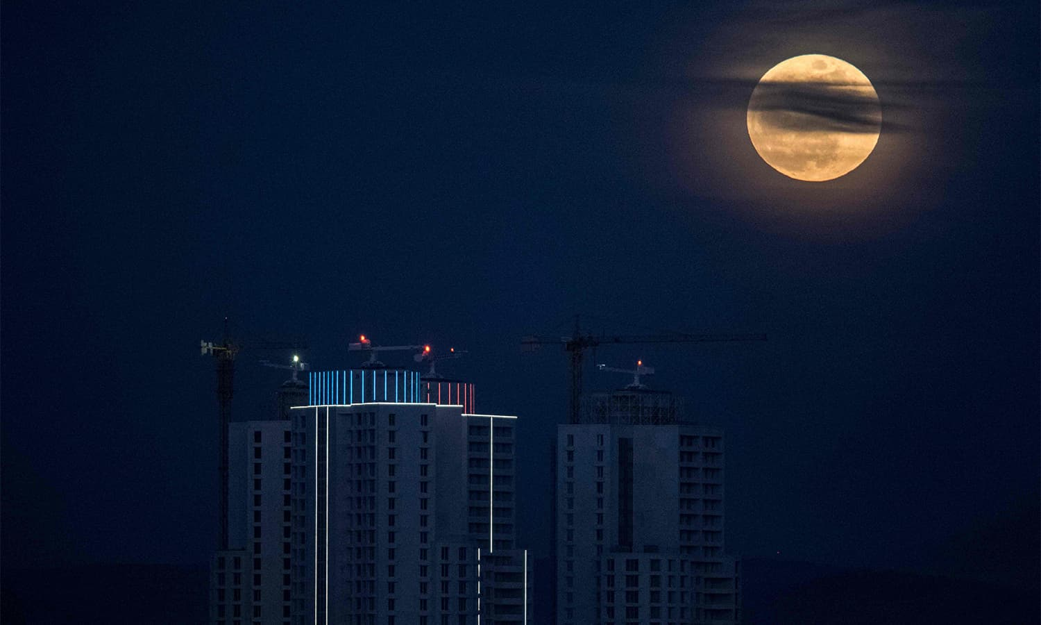 The moon rises next to the city's highest buildings in Skopje.— AFP