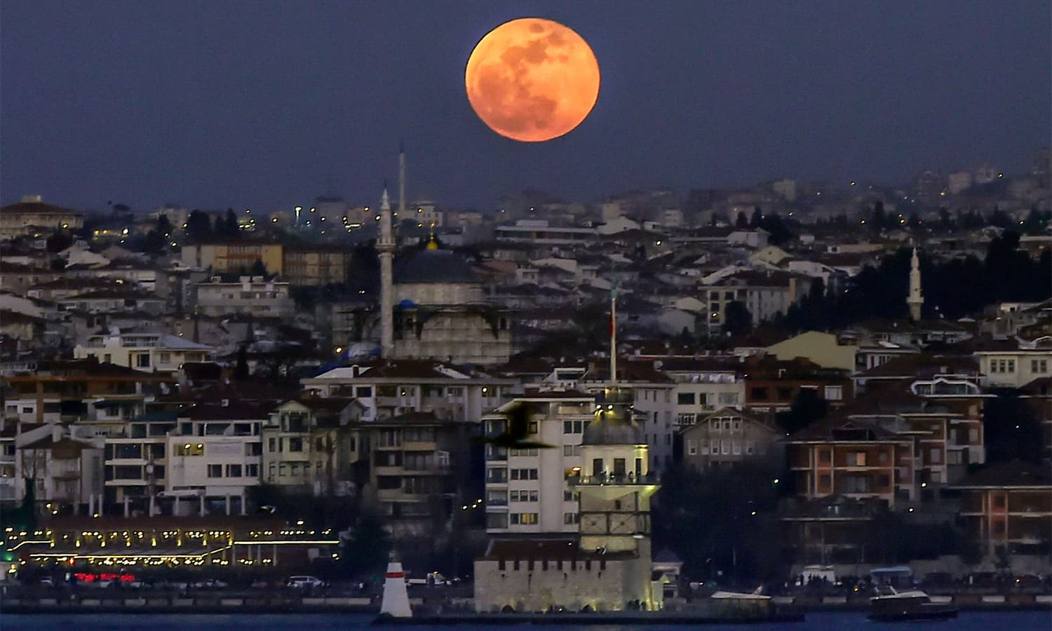 A picture shows the moon during a lunar eclipse up in the sky above the Bosphorus straits in Istanbul.— AFP