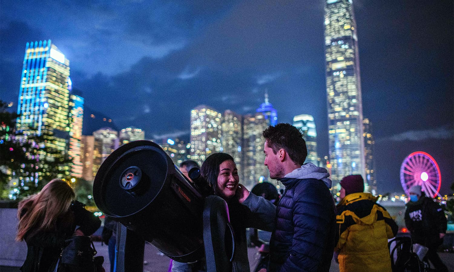 People set up telescopes near Victoria Harbour in the hope of seeing a 'supermoon' on a cloudy evening in Hong Kong on January 31.— AFP