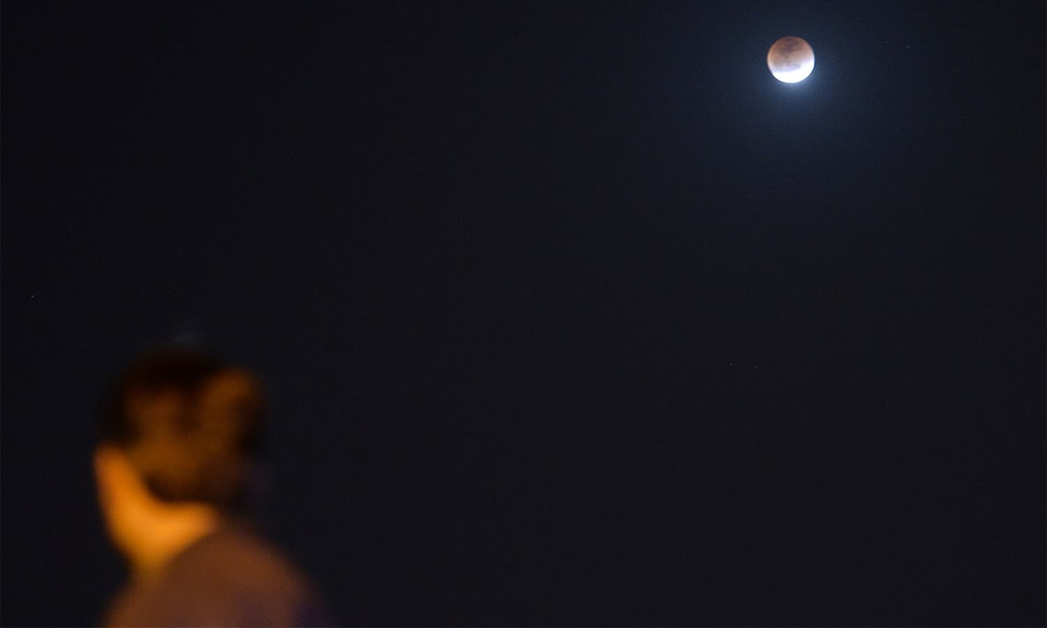 A resident watches the moon during a lunar eclipse in Islamabad.— AFP