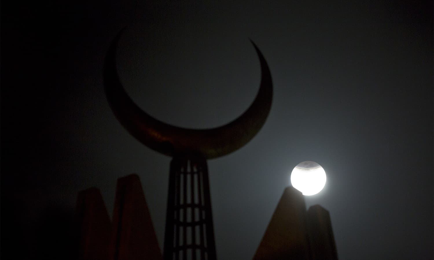 The partially-eclipsed moon rises against a crescent mounted on Faisal mosque in Islamabad.— AP