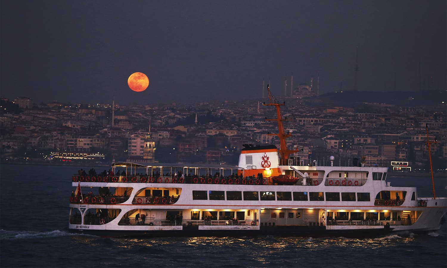 A boat sails in the Bosporus Strait separating Europe and Asia, as a supermoon rises over Istanbul on Wednesday.— AP