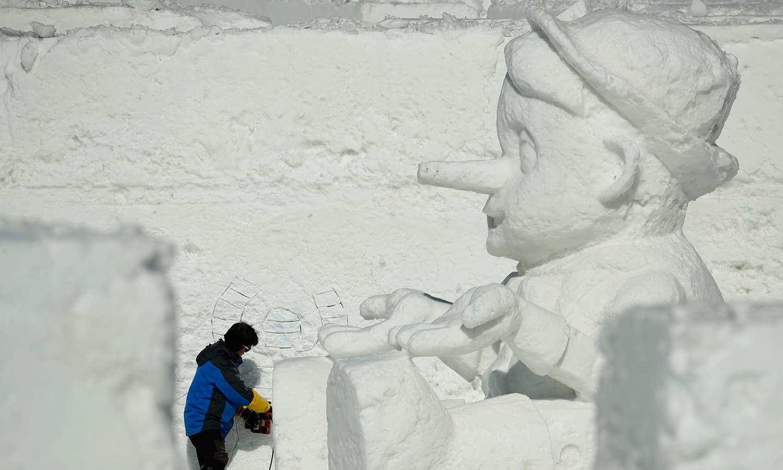 ایک آرٹسٹ برف کے دیدہ زیب ماڈل بنا رہا ہے— فوٹو: اے پی