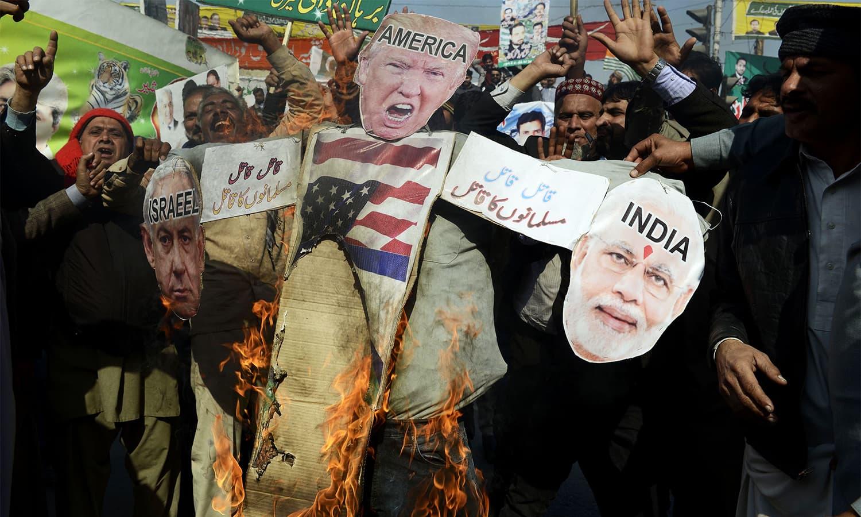 Demonstrators burn effigies of Netanyahu, Modi and Trump. — AFP