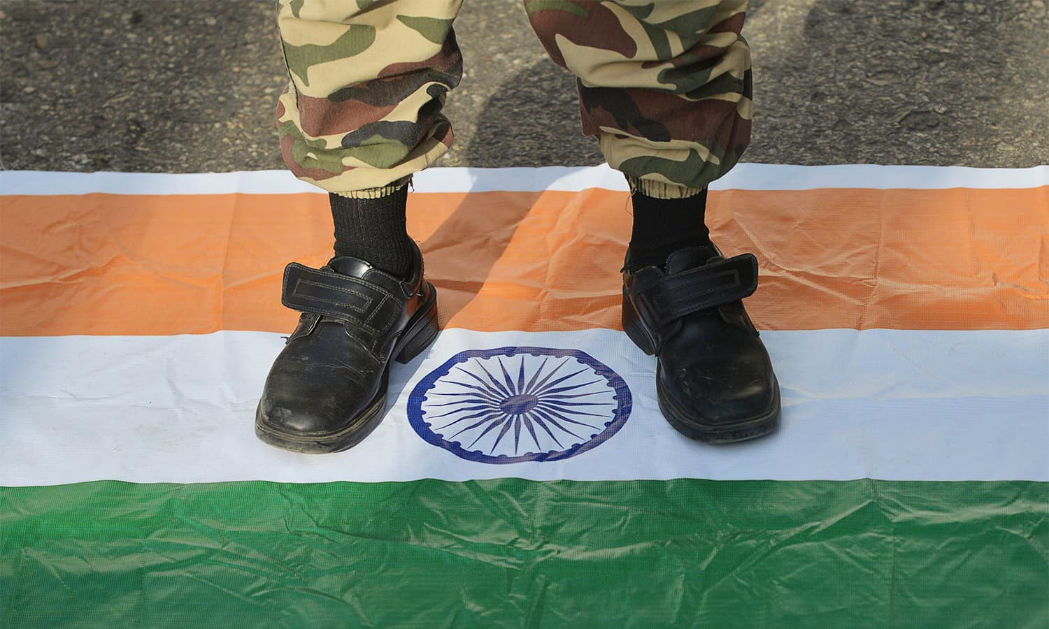 A protester stands on an Indian flag in Karachi. — AFP