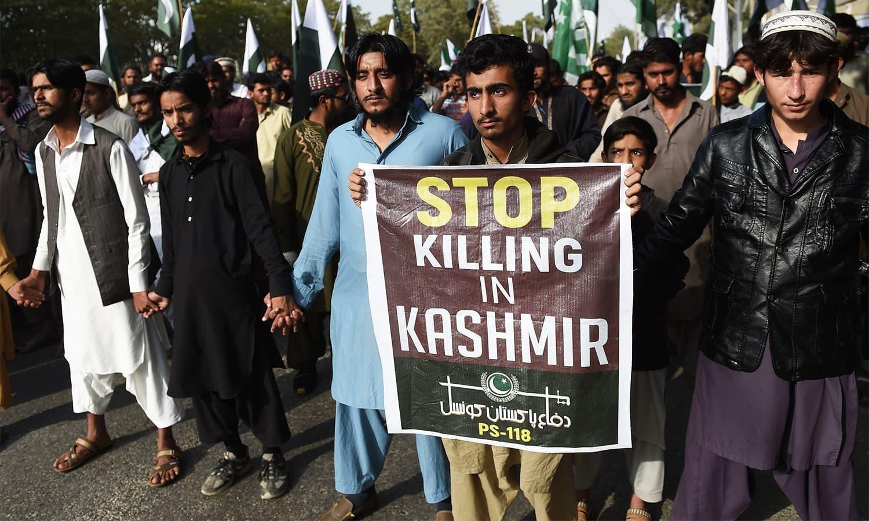 مظاہرین کشمیر میں قتل و غارت بند کرنے کا بینر لیے کھڑے ہیں — فوٹو: اے ایف پی