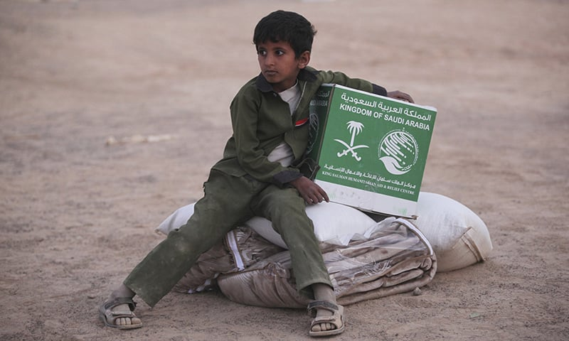 In this photograph, a young Yemeni boy living in a camp for people displaced by his country's war holds a box of aid from Saudi Arabia in Marib, Yemen. Saudi Arabia. — AP