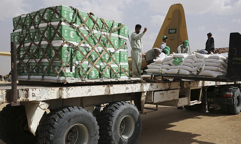 In this photograph, a relief worker signals a forklift driver unloading aid carried into Yemen by the Saudi military in Marib, Yemen. — AP