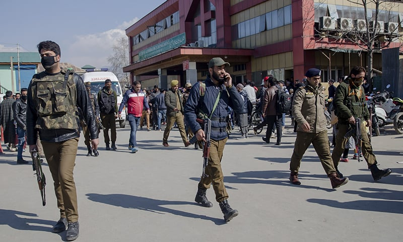 Indian police men escort ambulance carrying the body of a police officer who was killed after he was fired at inside a hospital in Srinagar. — AP