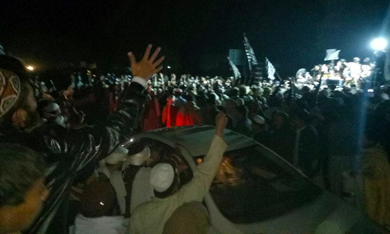 JUI-F workers gather around the car of one of the 26 acquitted people as he arrives in Mardan. — Photo by author