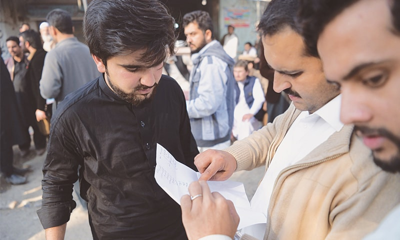 RELATIVES of some of the accused read a list of convicts outside the Haripur central jail.—AFP