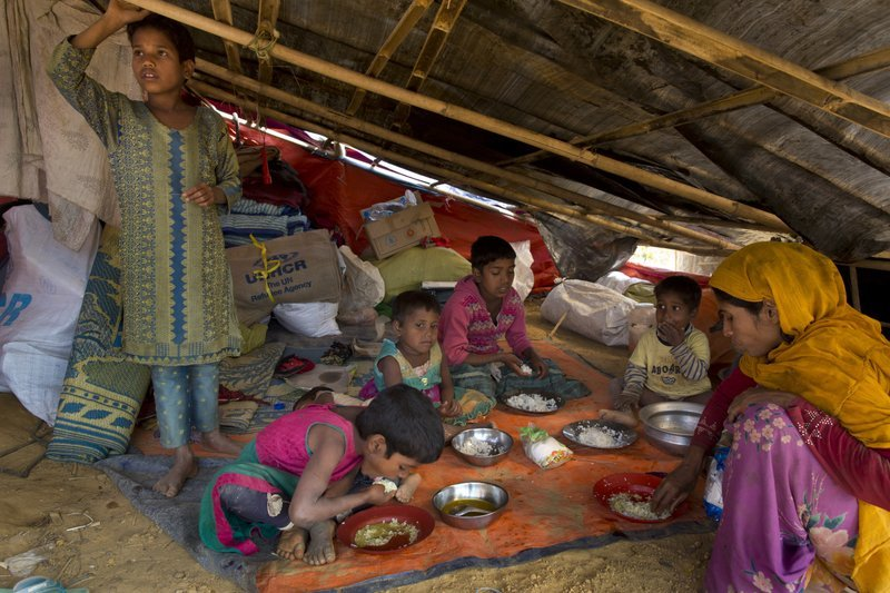 In this Jan 13 photo, a newly arrived Rohingya family eats at the Balukhali refugee camp near Cox's Bazar, Bangladesh.  — AP