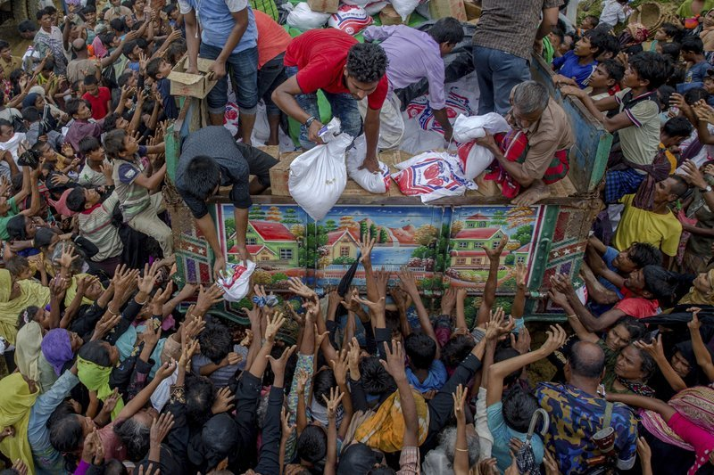 In this Sept 18, 2017, file photo, Rohingya Muslims, who crossed over from Myanmar into Bangladesh, reach out for food distributed by aid agencies near the Balukhali refugee camp in Cox's Bazar. ─ AP